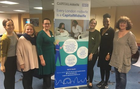 Midwives standing around Capital Midwife banner